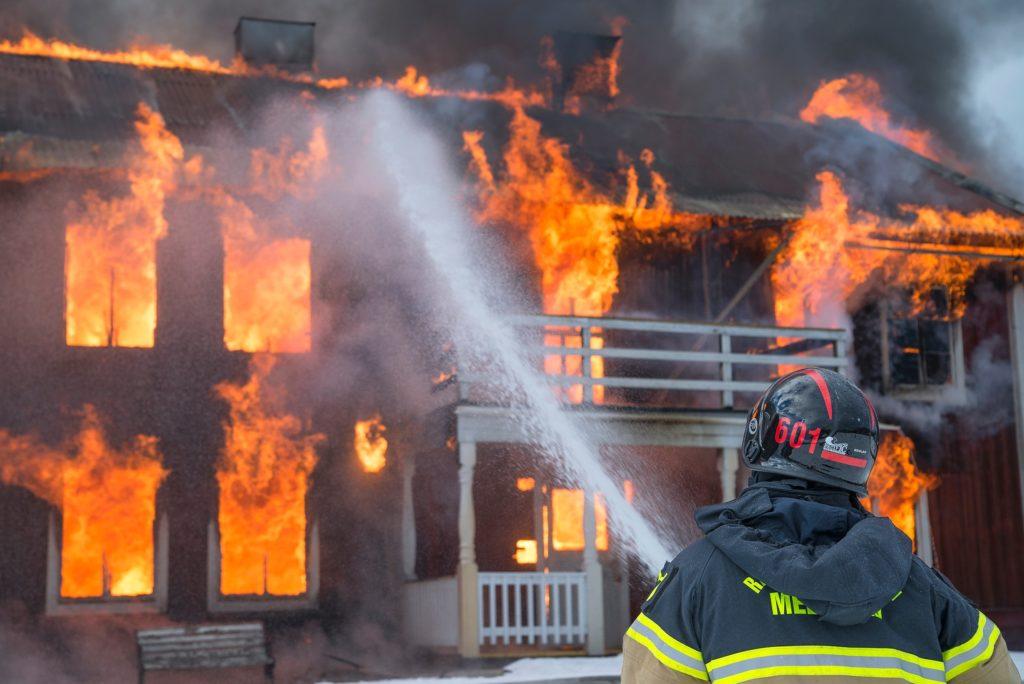 燃え盛る共同住宅と消防士