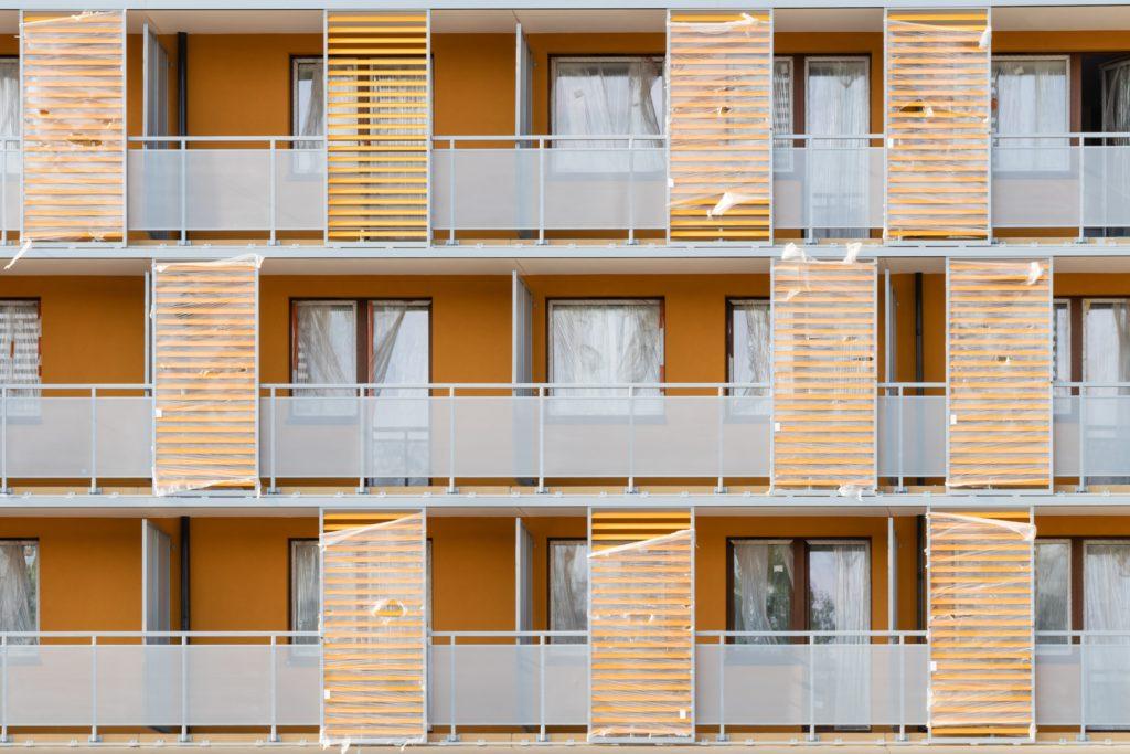 開放バルコニーと防風板の共同住宅
