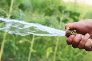 ホースの先端を押さえて放水圧力を高めている状況