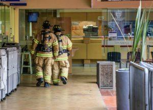 2人の消防隊員が建物内部を調査する様子